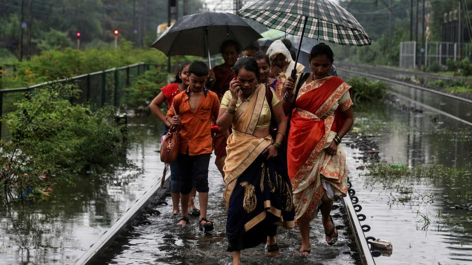 Commuters walk on waterlogged railway tracks after getting off a stalled train during heavy monsoon rains in Mumbai