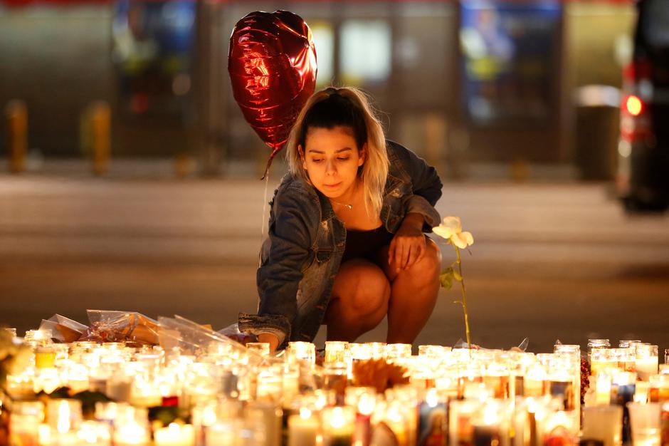A woman lights candles at a vigil on the Las Vegas strip following a mass shooting at the Route 91 Harvest Country Music Festival in Las Vegas | Autor: CHRIS WATTIE