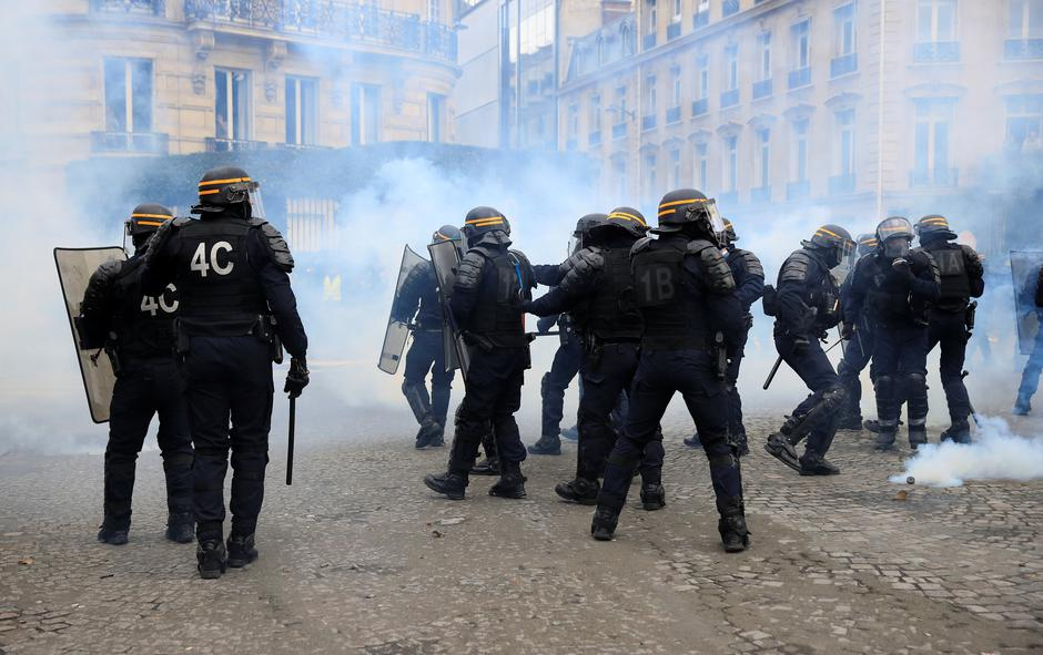 "Riot policemen react to tear gas during a demonstration by the ""yellow vests"" movement in Paris 