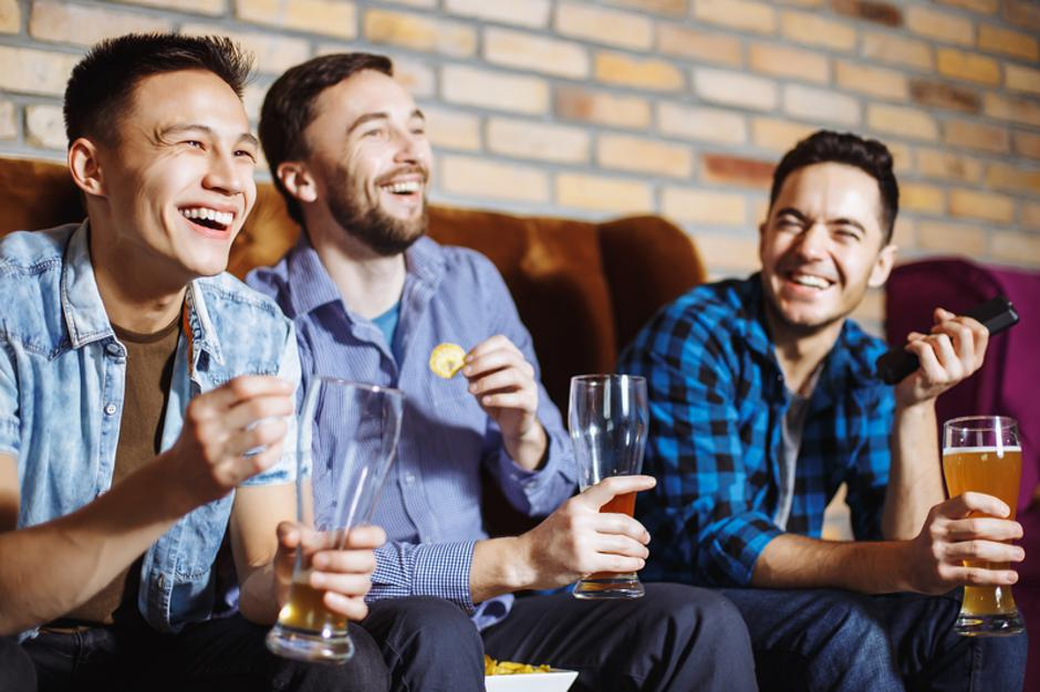 Friendship, sports and entertainment concept - happy male friends with beer watching tv at home. | Autor: Dreamstime