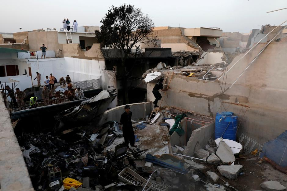 People stand on a roof of a house amidst debris of a passenger plane, crashed in a residential area near an airport in Karachi | Autor: AKHTAR SOOMRO/REUTERS/PIXSELL/REUTERS/PIXSELL