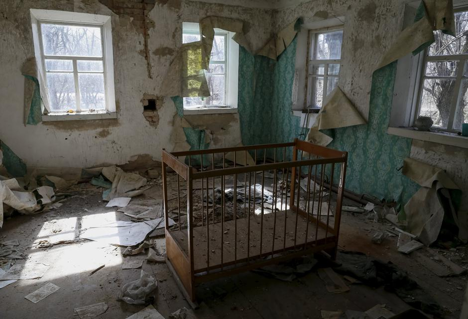 А baby cot is seen in a house in the abandoned village of Zalesye near the Chernobyl nuclear power plant | Autor: GLEB GARANICH