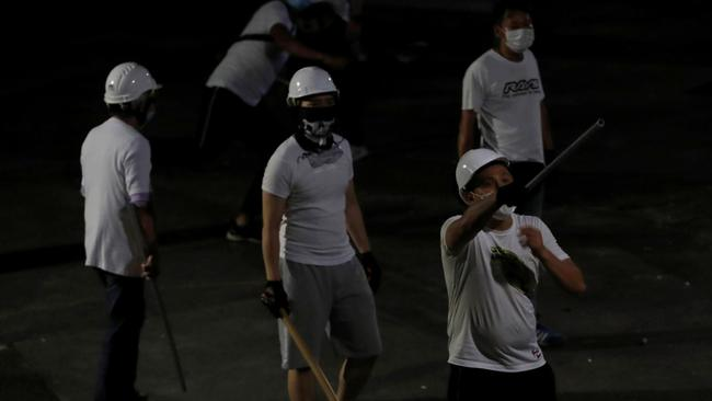 Men in white T-shirts react in Yuen Long after attacking anti-extradition bill demonstrators at a train station in Hong Kong