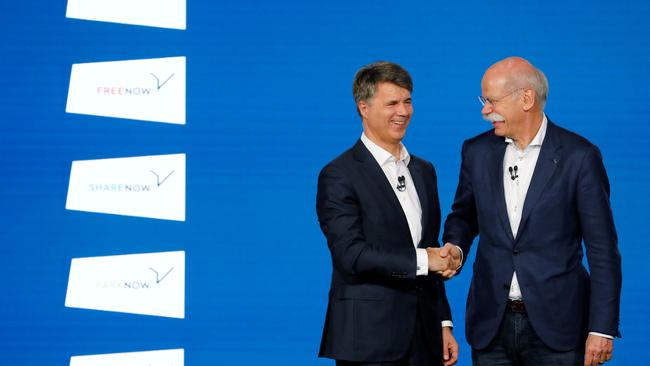 Harald Kruger, CEO and Chairman of the Board of Management of BMW AG and Dieter Zetsche, CEO of Daimler AG, shake hands at a news conference to present plans for combining the companies' car-sharing businesses, in Berlin