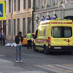 An ambulance is parked near a damaged taxi, which ran into crowds of people in central Moscow