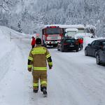 A member of the fire brigade walks on a closed road after heavy snowfall near Obertauern