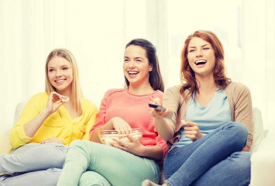 three smiling teenage girl watching tv at home | Autor: