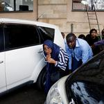 People are evacuated by a member of security forces at the scene where explosions and gunshots were heard at the Dusit hotel compound, in Nairobi