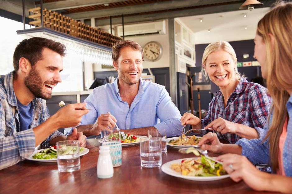 Group of friends eating at a restaurant | Autor: monkeybusinessimages