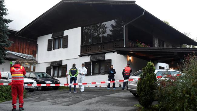 Police officers and rescue workers stand in front of a house where, according to police, five people were found dead in Kitzbuehel