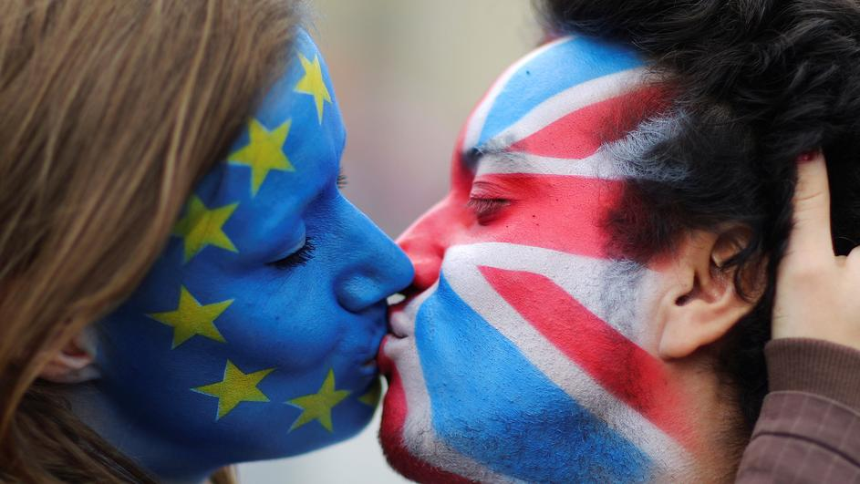 Two activists with the EU flag and Union Jack painted on their faces kiss each other in front of Brandenburg Gate to protest against Brexit in Berlin