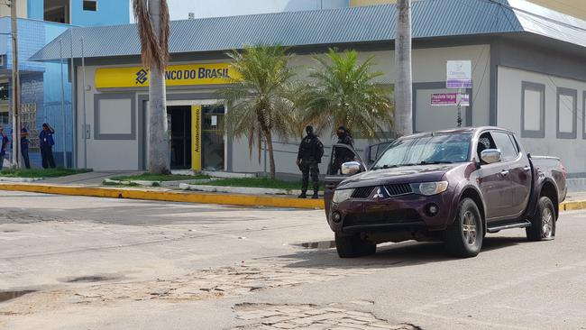 Policemen stand in front of the Banco do Brasil branch after a shootout between police and bank robbers, in Milagres