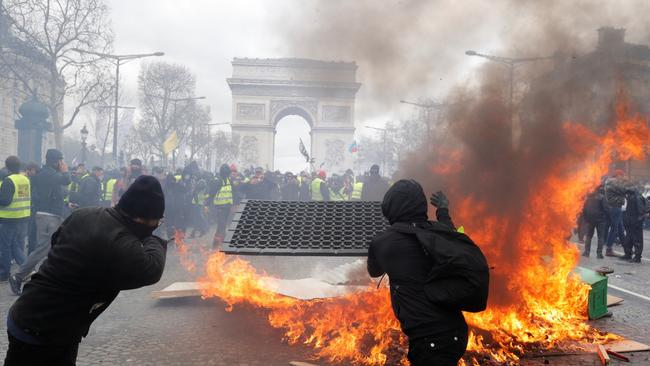 "Protesters react next to a burning barricade during a demonstration by the ""yellow vests"" movement in Paris"