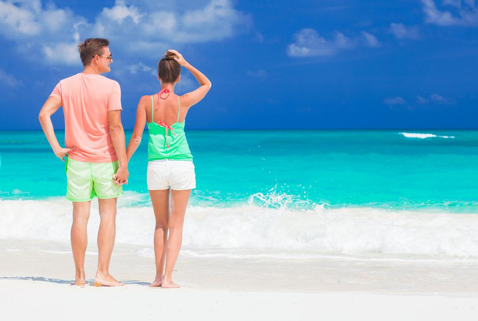 back view of happy romantic young couple holding hands on the beach | Autor: Dreamstime